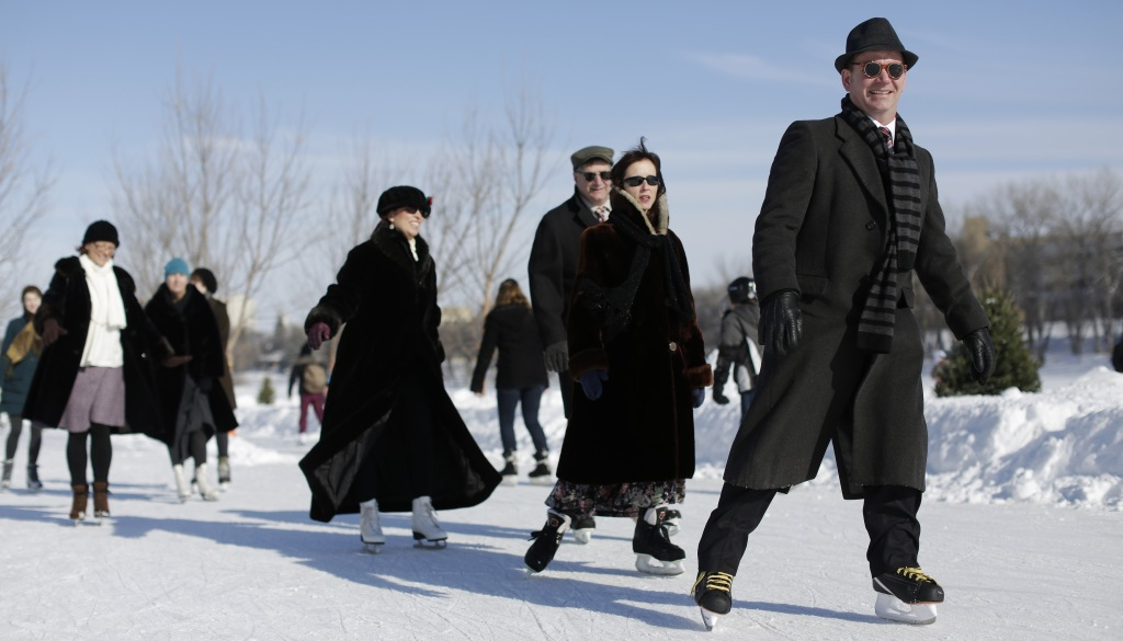 Skaters in period dress make their way along a river trail near the historic site of the Forks, the confluence of the Red and Assinibione rivers in Winnipeg, Manitoba