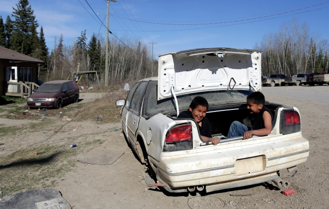 Boys play in an abandon car next to the muster point where hundreds will search for the remains of Teresa Robinson on the Garden Hill First Nation Manitoba, May 23, 2015. Lyle Stafford for the Globe and Mail