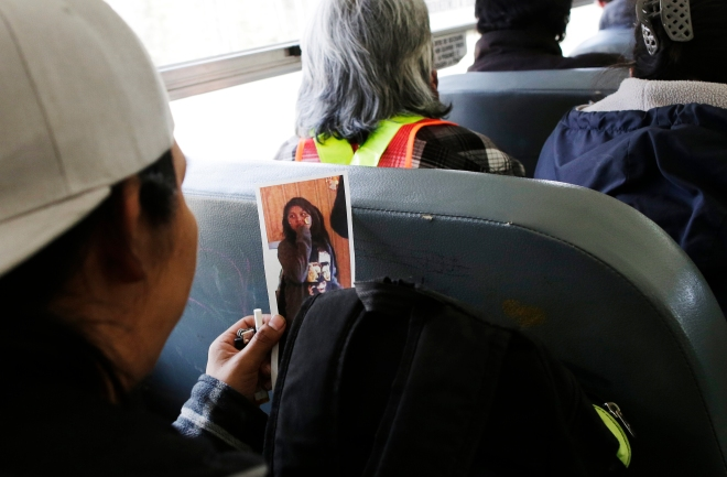 A volunteer looks at a photo of Teresa Robinson on a school bus while being transported to a search site on the Garden Hill First Nation Manitoba, May 22, 2015. Lyle Stafford for the Globe and Mail